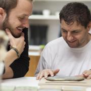 Zwei Männer beugen sich über einen Tisch und lachen.